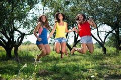 Tres muchachas que llevan a cabo las manos que saltan en jardín del verano Fotos de archivo libres de regalías