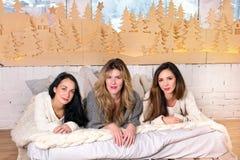Tres muchachas que ponen en la cama en la sonrisa acogedora de los suéteres Imágenes de archivo libres de regalías