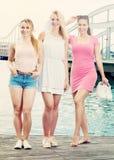 Tres muchachas que se colocan en la costa Imágenes de archivo libres de regalías