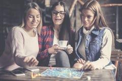 Tres muchachas que se divierten y que juegan al juego fotos de archivo