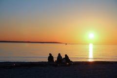 Tres muchachas que se relajan en la playa que mira la puesta del sol fotos de archivo libres de regalías
