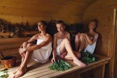 Tres muchachas que se relajan en sauna Imágenes de archivo libres de regalías