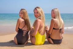 Tres muchachas que se sientan en la playa que mira detrás Fotos de archivo
