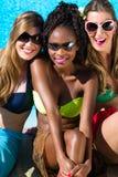 Tres muchachas que se sientan en piscina en el verano que se relaja Foto de archivo libre de regalías