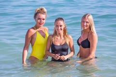 Tres muchachas que se unen en agua de mar Imágenes de archivo libres de regalías