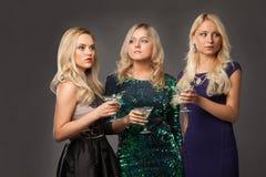 Tres muchachas rubias que llevan los vestidos de noche driknking martini fotografía de archivo