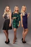 Tres muchachas rubias que llevan los vestidos de noche driknking martini imágenes de archivo libres de regalías