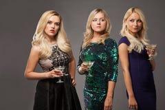 Tres muchachas rubias que llevan los vestidos de noche driknking martini Imagenes de archivo