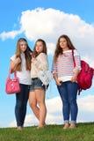 Tres muchachas se colocan con los bolsos en hierba Imágenes de archivo libres de regalías
