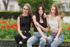 Tres muchachas se sientan en el fondo del parque Fotos de archivo libres de regalías