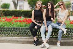 Tres muchachas se sientan en el fondo del parque Fotos de archivo