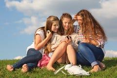 Tres muchachas se sientan en hierba con los teléfonos móviles Fotos de archivo libres de regalías