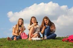 Tres muchachas se sientan en hierba con los teléfonos móviles Imagen de archivo libre de regalías