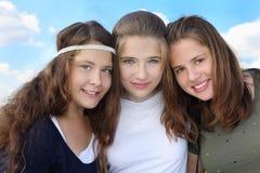 Tres muchachas sonrientes abrazan en el fondo del cielo Foto de archivo