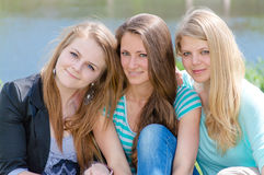 Tres muchachas sonrientes felices que abrazan contra el agua Imágenes de archivo libres de regalías