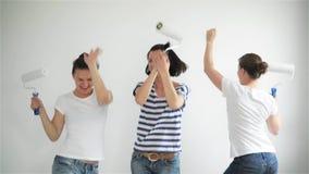 Tres muchachas sonrientes felices que bailan y que pintan la pared en sala de estar junto almacen de metraje de vídeo