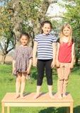 Tres muchachas sonrientes que se colocan en la tabla Imagenes de archivo