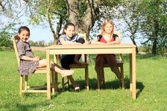 Tres muchachas sonrientes que se sientan alrededor de la tabla Imagenes de archivo