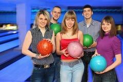Tres muchachas y dos hombres sostienen la bola para el bowling Imagenes de archivo
