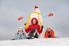 Tres muchachas y muñeco de nieve Foto de archivo libre de regalías