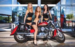 Tres muchachas y una motocicleta Foto de archivo libre de regalías