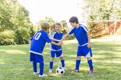 Tres, muchacho joven con el balón de fútbol en un uniforme del deporte Foto de archivo libre de regalías