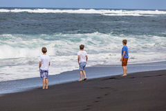 Tres muchachos adolescentes caminan a lo largo de una playa volcánica negra Fotografía de archivo