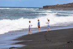 Tres muchachos adolescentes caminan a lo largo de una playa volcánica negra Fotografía de archivo libre de regalías