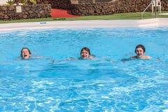 Tres muchachos adolescentes que nadan en una piscina Imagen de archivo libre de regalías