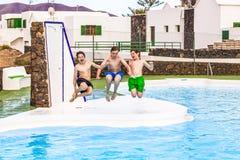 Tres muchachos adolescentes que saltan en la piscina Fotos de archivo