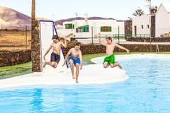 Tres muchachos adolescentes que saltan en la piscina Imagen de archivo