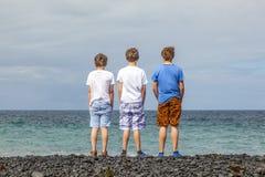 Tres muchachos adolescentes se colocan en una playa volcánica negra Foto de archivo libre de regalías