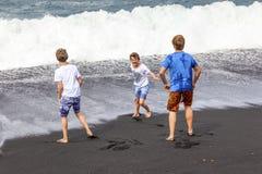Tres muchachos adolescentes se divierten en una playa volcánica negra Fotografía de archivo
