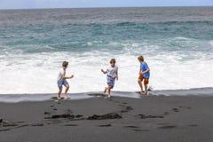 Tres muchachos adolescentes se divierten en una playa volcánica negra Foto de archivo