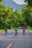 Tres muchachos con diversas camisas del color que montan las bicicletas Foto de archivo libre de regalías