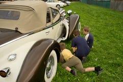 Tres muchachos debajo de los veteranos del coche Foto de archivo