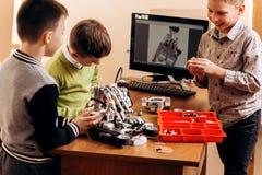 Tres muchachos elegantes están haciendo los robots del constructor robótico en la escuela de la robótica foto de archivo libre de regalías
