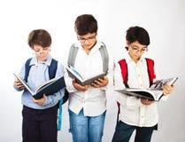Tres muchachos elegantes leyeron los libros Imágenes de archivo libres de regalías