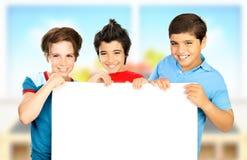 Tres muchachos en la sala de clase que lleva a cabo a la tarjeta limpia blanca Foto de archivo