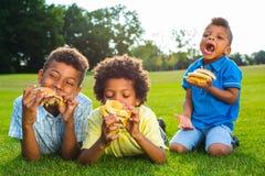 Tres muchachos están comiendo fotografía de archivo