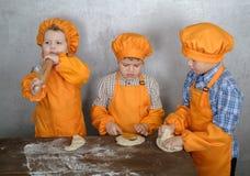 Tres muchachos europeos lindos vestidos como cocineros están ocupados el cocinar de la pizza tres hermanos ayudan a mi madre a co foto de archivo