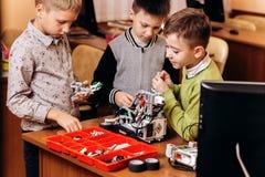 Tres muchachos felices están haciendo los robots en la escuela de la robótica foto de archivo
