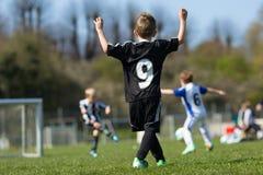 Tres muchachos jovenes que juegan a fútbol Imagenes de archivo