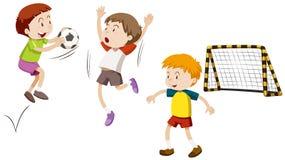 Tres muchachos que juegan a fútbol Imagen de archivo libre de regalías
