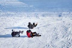 Tres muchachos que montan en diapositivas de la nieve en invierno fotografía de archivo