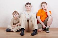 Tres muchachos se sientan en suelo con sus piernas metidas para arriba Foto de archivo libre de regalías