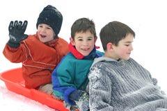 Tres muchachos Sledding Foto de archivo libre de regalías