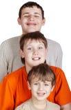 Tres muchachos sonrientes se colocan uno tras otro Foto de archivo