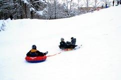 Tres muchachos van abajo de la colina en un trineo imagen de archivo