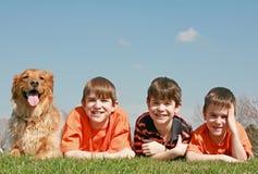Tres muchachos y un perro fotografía de archivo